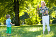 Grandmother and her grandson playing with soap bubbles