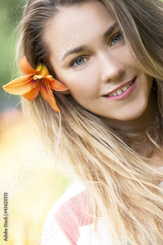 Smiling girl with lily flower in hair