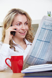 Frau liest Zeitung und telefoniert