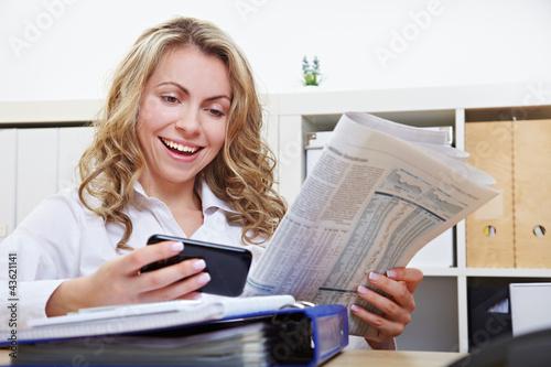 Frau mit Smartphone liest Zeitung