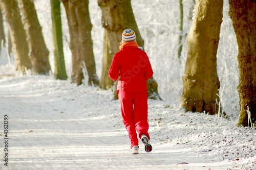 Joggerin auf einem verschneiten Waldweg