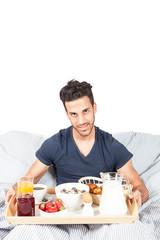 Man is having breakfast in the bed