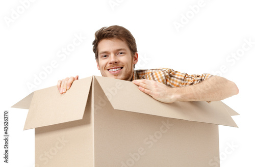 Pretty man hides inside the cardboard box, isolated