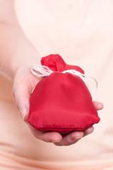 Hand hält ein rotes Säckchen