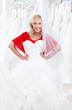 Agitated girl puts a wedding gown to her body