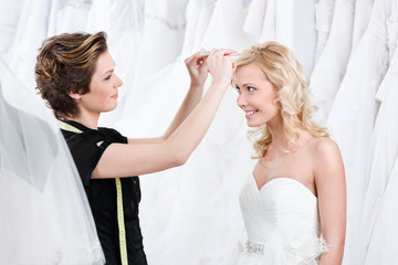 Shop assistant helps to fix the wedding tiara, white background