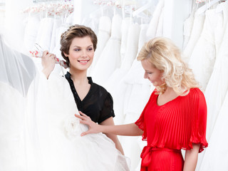 Two girls have a good look at the wedding dress
