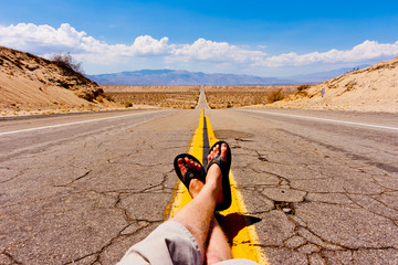 Man resting in the middle of a desert highway.