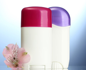 deodorants with flower on blue background