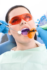 Dentist uses photopolymer lamp and dental mirror