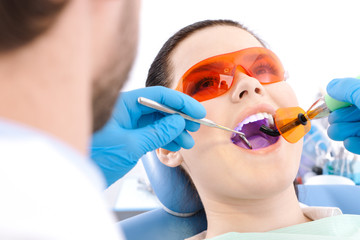 Dentist uses photopolymer lamp to cure carious teeth