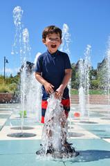 Young boy playing in a splashing fountain