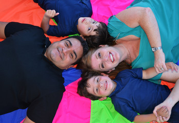 A family posing on the ground on colorful background