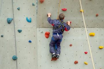 Junge in der Kletterwand