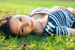 Closeup of a beautiful young woman lying in grass
