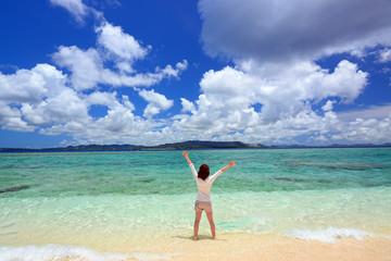 南国の美しいビーチで遊ぶ女性