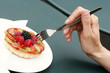 A hand holding a fork poking a fruit pie