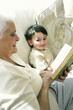 An old woman sitting on the couch reading book while her grandson is sitting beside her