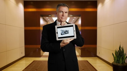 Businessman holds tablet that shows success