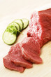 Beef and cucumber slices on a chopping board