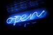 Blue neon open sign illuminating under the dark