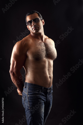 portrait of topless athletic man posing over black background