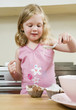 Girl pouring flour mixture on cupcakes