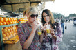 Women enjoying fresh orange juice at beverage stall