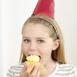 Girl in party hat eating cupcake