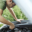 Man looking under car hood, fixing car with pliers