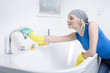 Woman with rubber gloves, cleaning the faucet