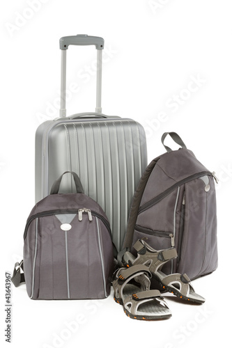 Silver travel suitcase, two gray backpacks and travel shoes