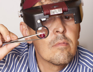 Male jeweler looking in a ruby.  Focus on ruby