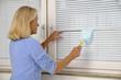 Frau wischt Staub von Fensterjalousien