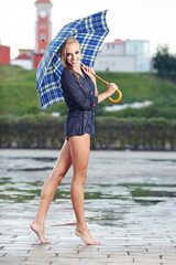 Sexy girl under umbrella watching the rain