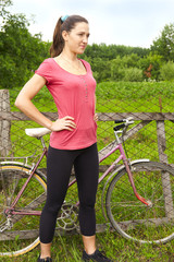 Portrait of pretty young woman with bicycle in a park - outdoor
