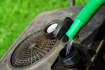 Benzin in den Rasenmäher füllen