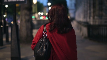 Happy woman walking in the city in the evening, steadicam shot