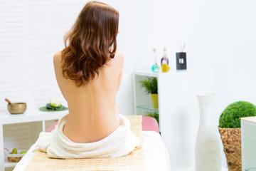 junge frau sitzt entspannt auf de massageliege