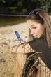 junge Frau (17) mit Mobiltelefon am Bade-See