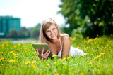 Fototapety Beautiful smiling woman with tablet pc, outdoors