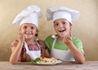 Happy kids with chef hats eating fresh pasta