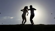 Romantic scene:  happy couple dancing over sun with flying birds