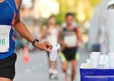 Marathon racer catching cup of water