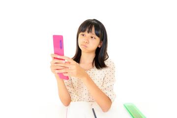 携帯電話を持ち不満そうな表情をする受験生