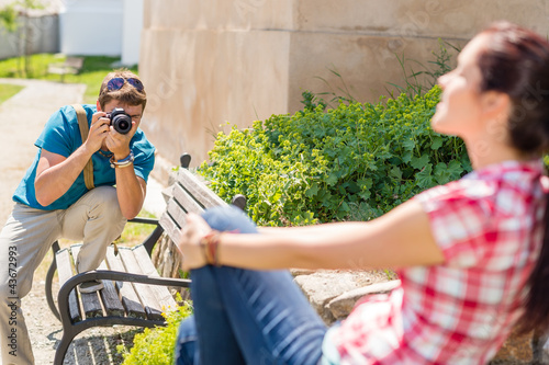 Man taking pictures of woman on bench