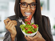 african happy businesswoman eating salad at office