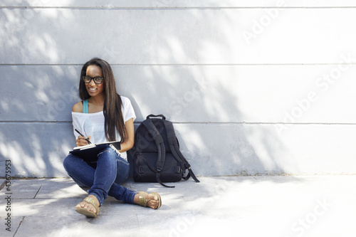 African American university woman studying at the park
