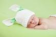 Funny sleeping newborn child. Bunny cap on head of girl.
