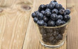 Blueberries in a glass on wood